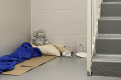 Home Sweet Hell. A homeless person's makeshift bed and some belongings under a stairwell royalty free stock images