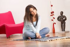 Home sweet home. Young lady with long dark brown hair, blue top and jeans, sitting on the floor of her living room Royalty Free Stock Images