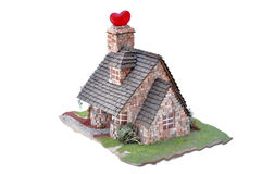 Home, sweet home. Miniature of a cottage with a red heart in the chimney Royalty Free Stock Images