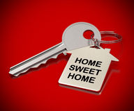 Home sweet home. Written onto a metal keyring, home shape. metallic key over red background Royalty Free Stock Photography