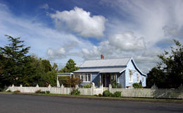 Home Sweet Home. Blue painted house with picket fence and dramatic sky royalty free stock photo