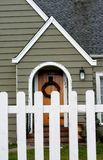 Home sweet home. Cottage style house with wreath on door, picket fence stock image