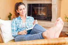 Home sweet home. Beautiful woman at home relaxing while reading royalty free stock images