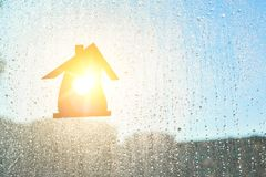 Home Sweet Home. Home symbol with  heart shape on a window background with sunny drops of rain Royalty Free Stock Photography