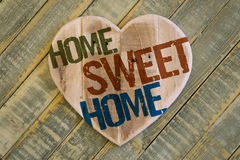 Home Sweet Home message wooden heart on light green painted back Stock Images