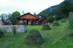 Home sweet home. Mountain cottage, newly mown grass and miss home Stock Images