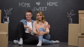 Home sweet home phrase on wall, happy family smiling at camera, mortgage. Stock footage stock video footage