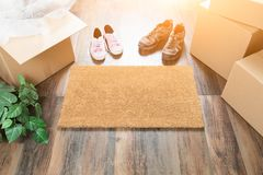Home Sweet Home Welcome Mat, Moving Boxes, Women and Male Shoes Stock Photography