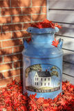 Home Sweet Home  Welcoming Milk Can Covered With Fallen Leaves. Large old fashioned milk can sits on front porch of home surrounded by bright red fallen autumn Stock Photography