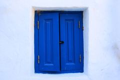 Home sweet home: white house with blue wooden window. A white house with blue windows which is very typical of the greece region stock image