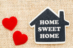 Home sweet home. Home sweet home word in wooden home model with red heart on sack background stock images