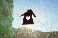 Home symbol with a heart shape on a window background with sunny drops of rain Stock Image