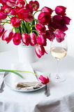 Home table setting with bright pink tulips. Home table setting with a bouquet of bright pink tulips in a white vase, cutlery and a glass of wine isolated Royalty Free Stock Images