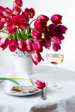 Home table setting with bright pink tulips. Home table setting with a bouquet of bright pink tulips in a white vase, tablecloth, cutlery and a glass of wine Royalty Free Stock Photo