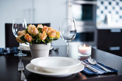 Home table setting. Simple home table setting with flowers, glasses and cutlery in the kitchen interior Stock Photos