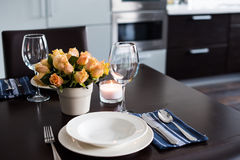 Home table setting. Simple home table setting with flowers, glasses and cutlery in the kitchen interior Stock Photo