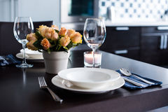 Home table setting. Simple home table setting with flowers, glasses and cutlery in the kitchen interior Royalty Free Stock Images