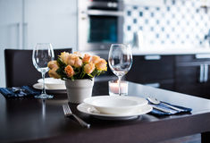 Home table setting. Simple home table setting with flowers, glasses and cutlery in the kitchen interior Royalty Free Stock Photo