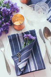 Home table setting. Vintage home table setting with blue napkins, antique cutlery, old key and purple cornflowers on white wooden table Royalty Free Stock Photos