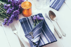 Home table setting. Vintage home table setting with blue napkins, antique cutlery, old key and purple cornflowers on white wooden table Royalty Free Stock Images