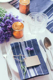 Home table setting. Vintage home table setting with blue napkins, antique cutlery and purple cornflowers on white wooden table. Blank cardboard tag and an old Stock Photos