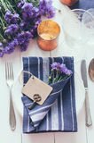 Home table setting. Vintage home table setting with blue napkins, antique cutlery and purple cornflowers on white wooden table. Blank cardboard tag and an old Stock Photo