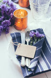 Home table setting. Vintage home table setting with blue napkins, antique cutlery and purple cornflowers on white wooden table. Blank cardboard tag Stock Images