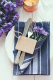 Home table setting. Vintage home table setting with blue napkins, antique cutlery and purple cornflowers on white wooden table. Blank cardboard tag Royalty Free Stock Images