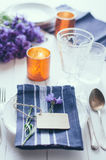 Home table setting. Vintage home table setting with blue napkins, antique cutlery and purple cornflowers on white wooden table. Blank cardboard tag and an old Royalty Free Stock Image
