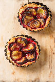 Home tartlets with plum on old wooden background Royalty Free Stock Photos
