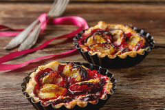 Home tartlets with plum on old wooden background Stock Photos
