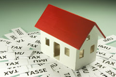 Home taxes. Model of a house with taxes Stock Photos