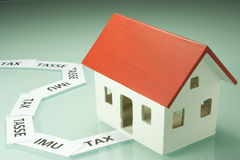 Home taxes. Model of a house with taxes Stock Image