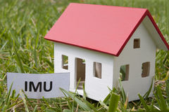 Home taxes imu. Model of a house with taxes Royalty Free Stock Photo