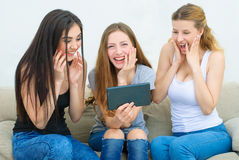 Home, technology and friendship concept - three smiling girl. Watching something on tablet Royalty Free Stock Images