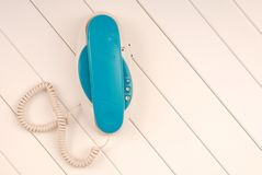 Home telephone is on white background, blue phone device is on t Royalty Free Stock Photos