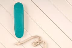 Home telephone is on white background, green phone device is on. Table, empty space and panel texturing backgrounds Stock Image