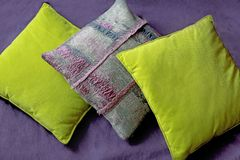 Three pillows on lilac background stock photos