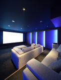 Home theater, luxury interior. Comfortable divan and big screen Stock Photography
