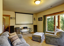 Home theater room with gray sofas and projector screen. Mountain home theater in cabin style home with carpet and projector screen stock photography