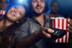 Home theater. Young men watching a movie with his girlfriend and pointing a remote control: cinema, entertainment and home theater concept Stock Images