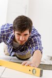 Home tile improvement - handyman with level. Laying down tile floor Royalty Free Stock Images