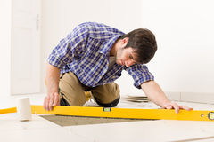 Home tile improvement - handyman with level Stock Photo