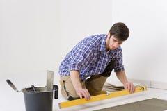 Home tile improvement - handyman with level Stock Image