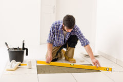 Home tile improvement - handyman with level Royalty Free Stock Photos