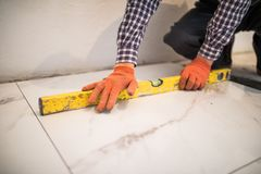 Home tile improvement - handyman with level laying down tile floor at home. Home tile improvement - handyman with level laying down tile floor stock photo