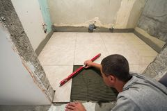 Home tiles improvement - handyman with level laying down tile floor. Renovation and construction concept. Home tiles improvement - handyman with level laying stock image
