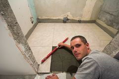 Home tiles improvement - handyman with level laying down tile floor. Renovation and construction concept. Home tiles improvement - handyman with level laying royalty free stock photography