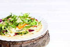 Home tortilla with fried egg, hummus and fresh salad variety on a plate. Easy vegetarian tortilla recipe. Healthy breakfast Stock Photos
