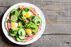 Home tortilla with fried quail eggs, avocado, cucumbers, beet hummus, sesame seeds and parsley on plate Royalty Free Stock Images
